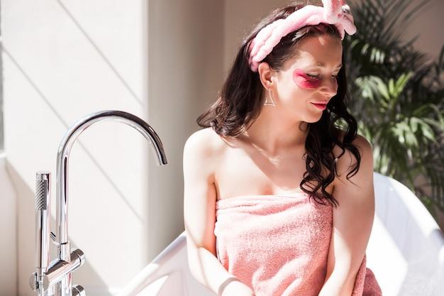 Bella giovane donna in un asciugamano rosa, con una benda cosmetica in testa, in posa davanti alla telecamera in un bagno soleggiato.