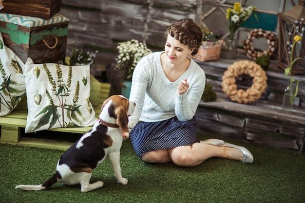 Bella giovane donna che gioca con un cane sulla casa di campagna