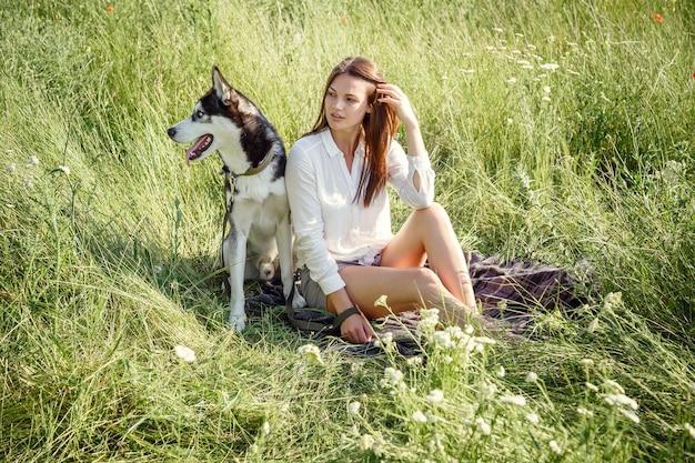 Bella giovane donna che gioca con il cane husky divertente all'aperto al parco