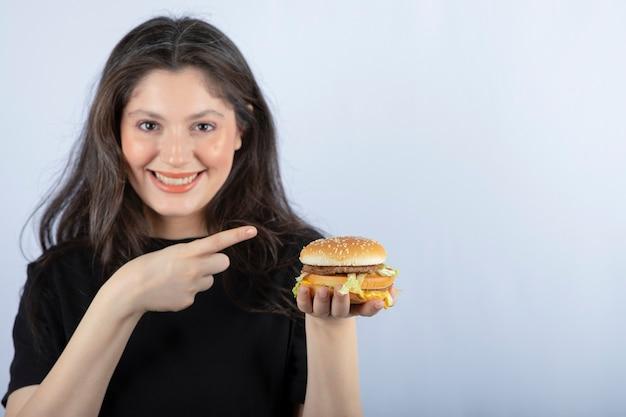 Bella giovane donna che indica hamburger di carne delizioso.