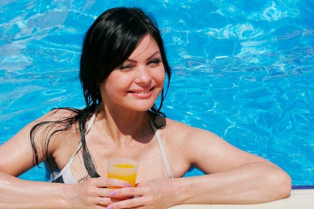 Bella giovane donna in una piscina