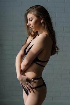 Bella e giovane donna che posa in biancheria sexy nera. interni d'epoca e sfondo retrò.