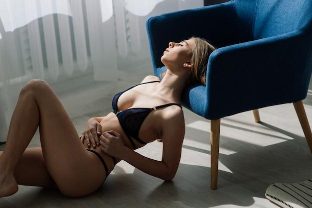 Bella e giovane donna che posa in biancheria sexy nera.
