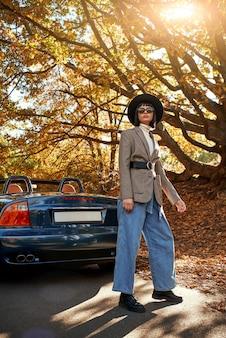 Bella giovane donna in posa vicino alla stagione autunnale cabriolet