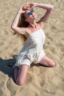 Bella giovane donna in posa su una spiaggia di sabbia.
