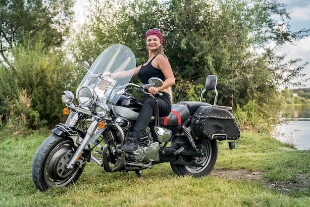 Bella giovane donna in posa con la moto all'esterno