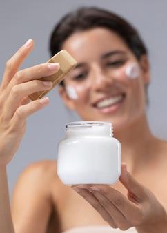 Bella giovane donna in posa con un prodotto per la cura della pelle
