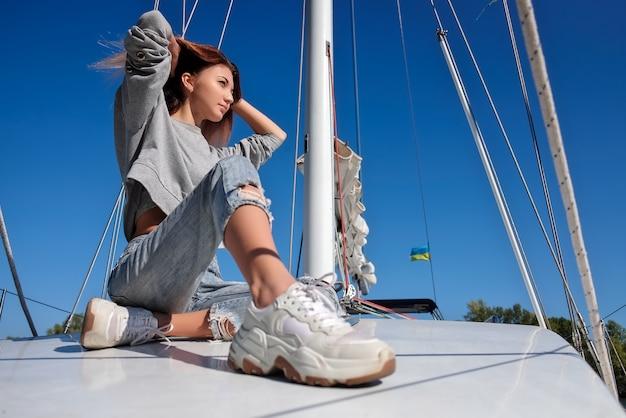 Bella giovane donna che posa sull'yacht.
