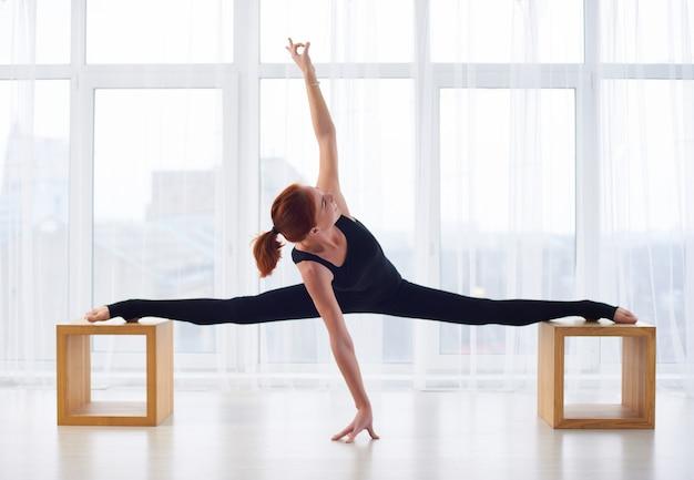 La bella giovane donna pratica l'asana di yoga allo studio di yoga