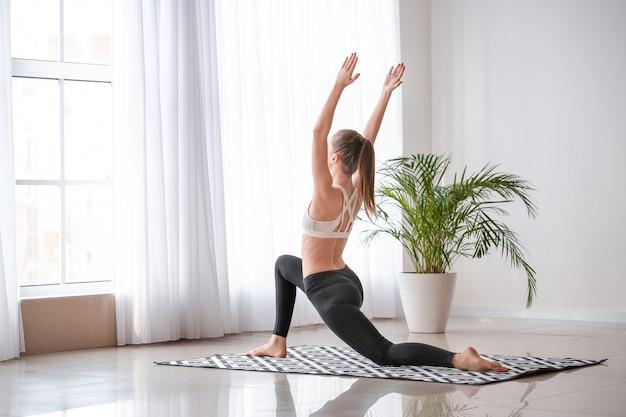 Bella giovane donna a praticare yoga a casa