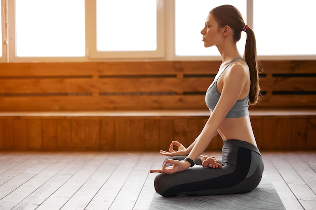 Bella giovane donna a praticare yoga nella posizione del loto