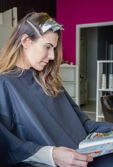 Bella giovane donna che legge una rivista mentre aspetta con la tintura per capelli in testa