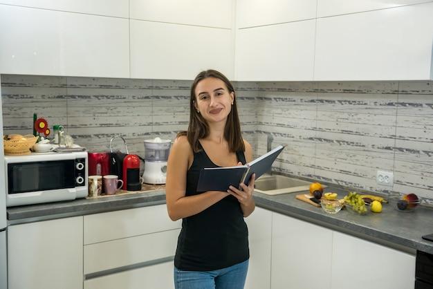 La bella giovane donna legge un taccuino in cucina per cucinare cibo sano per la colazione.