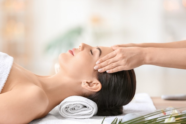 Bella giovane donna che riceve massaggio facciale nel salone della stazione termale?
