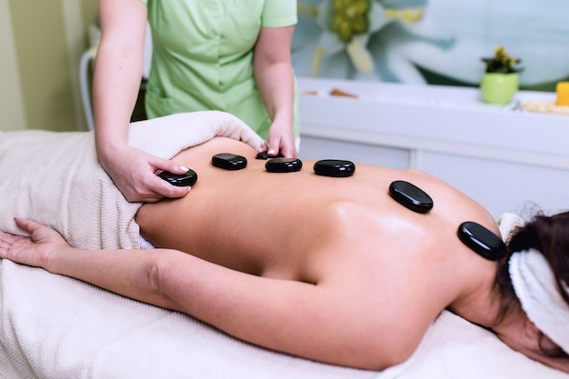 Bella giovane donna che riceve massaggio facciale con pietre calde presso il centro termale di bellezza. terapia lastone.
