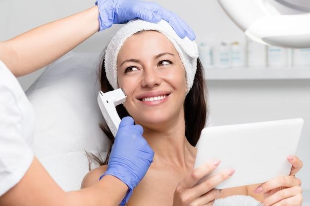 Bella giovane donna che riceve un trattamento per la rimozione di talpa presso una clinica di bellezza spa di lusso.