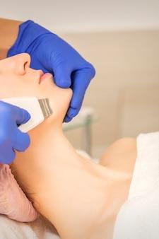Bella giovane donna che riceve la pulizia del viso a cavitazione ultrasonica nel salone della stazione termale di bellezza