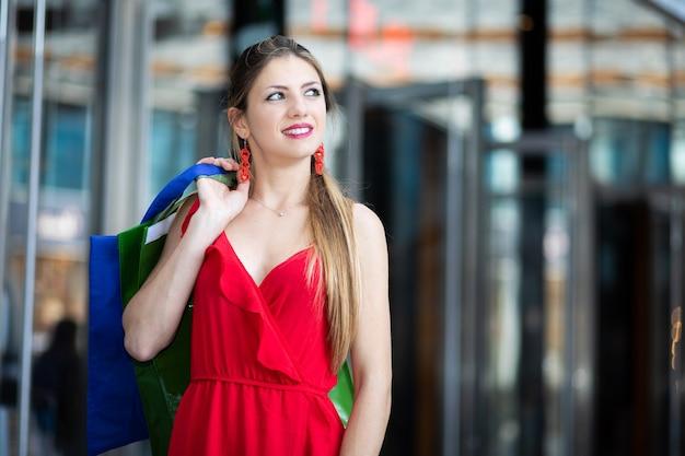 Bella giovane donna in un vestito rosso che tiene le borse della spesa e passeggiate all'aperto in un centro città