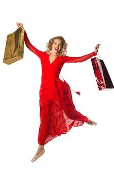Bella giovane donna in un abito rosso con i pacchetti nelle loro mani su uno sfondo bianco
