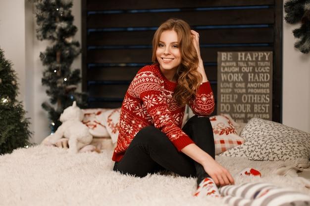 Bella giovane donna in maglione rosso alla moda si siede sul letto in camera da letto