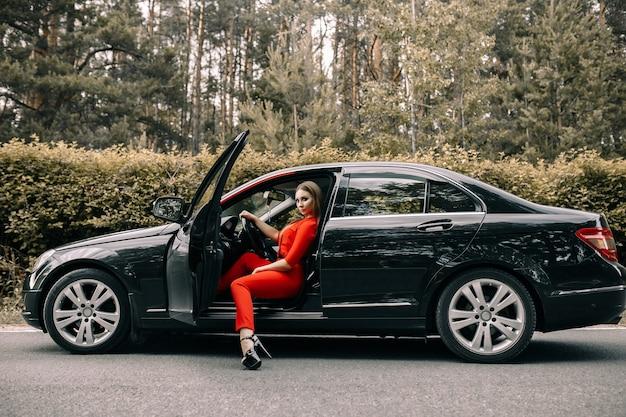 Una bella giovane donna in tuta rossa si siede al volante di un'auto nera su una strada deserta nella foresta