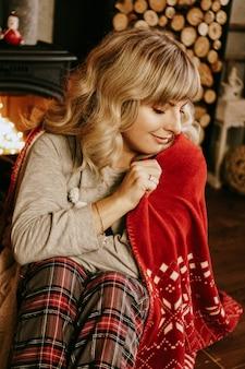 Una bella giovane donna in un plaid rosso si siede in un caldo interno classico di capodanno