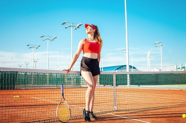 La bella giovane donna in vestiti di sport rossi che posano con la racchetta da tennis alla corte