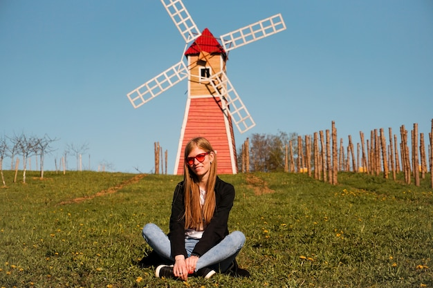 La bella giovane donna in occhiali da sole rossi si siede sull'erba sullo sfondo del mulino rosso.