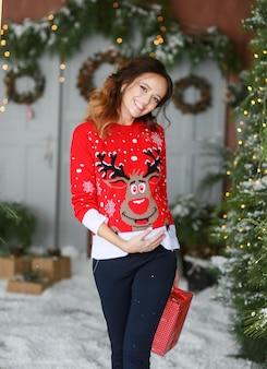 Una bellissima giovane donna in un maglione rosso si erge sullo sfondo di decorazioni natalizie