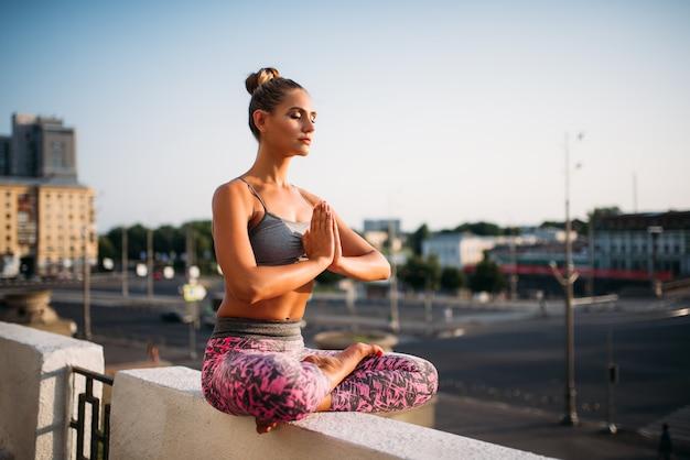 La bella giovane donna si rilassa nella posa di yoga, città. esercizio di meditazione yogi all'aperto