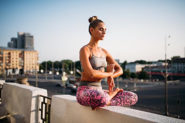La bella giovane donna si rilassa nella posa di yoga