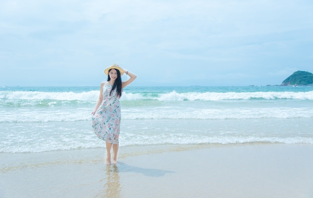 Bella giovane donna che si distende sulla spiaggia