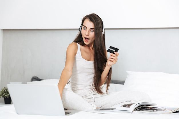 Bella giovane donna che si distende sul letto a casa, ascoltando la musica con le cuffie, utilizzando il laptop, mostrando la carta di credito