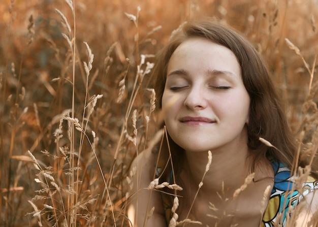 Bella giovane donna che si distende nell'erba
