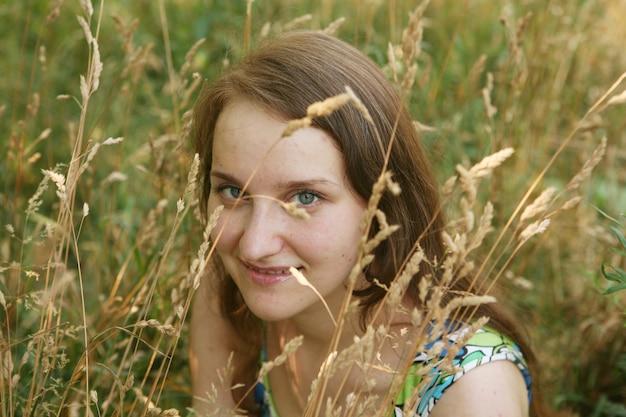 Bella giovane donna che si rilassa nell'erba