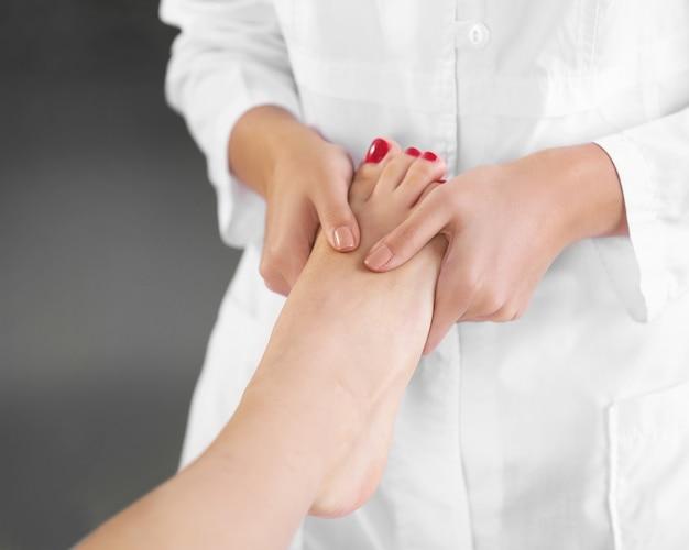Bella giovane donna che si distende con massaggio alle gambe presso il centro termale di bellezza