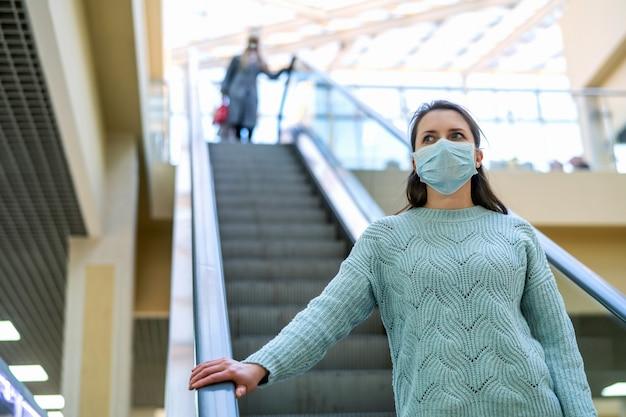 La bella giovane donna guida la scala mobile di un centro commerciale con la maschera protettiva