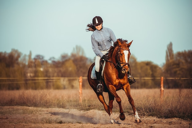 Una bella giovane donna a cavallo con un casco nero e stivali