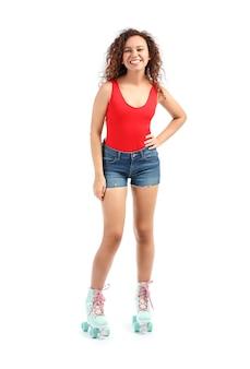 Bella giovane donna su pattini a rotelle contro white
