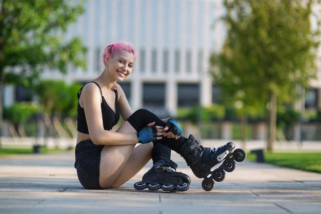 Bella giovane donna pattinaggio a rotelle all'aperto