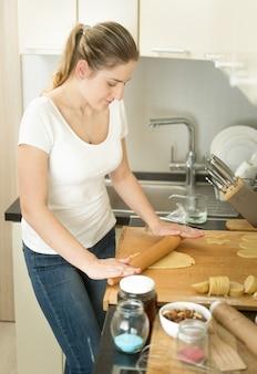Bella giovane donna che rotola la pasta con il perno di legno sulla cucina
