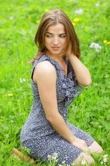 Bella giovane donna in abito romantico rilassante in giardino