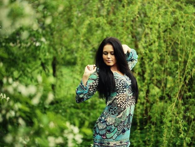 Bella giovane donna in abito romantico che si rilassa in giardino