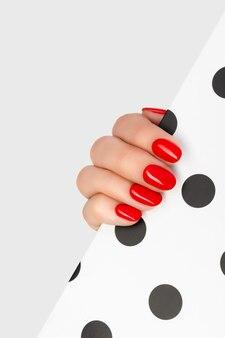 Mano della bella giovane donna con il manicure rosso su grigio