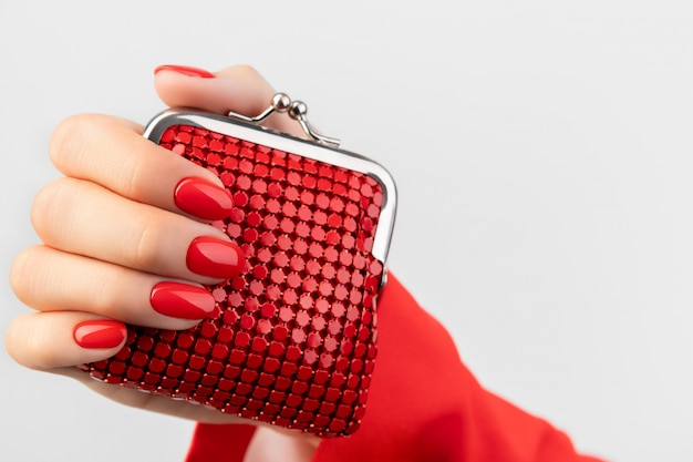 La mano della bella giovane donna con il manicure rosso tiene il portafoglio su gray