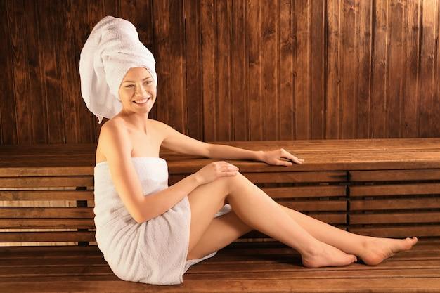 Bella giovane donna nella sauna sulla parete di legno