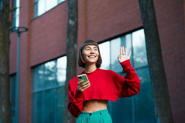 Bella giovane donna che dice ciao per strada e che tiene il telefono, donna carina millenial in maglione rosso elegante con smartphone in braccio e mostrando ciao gesto
