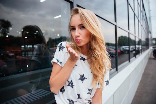 Bella giovane donna che manda un bacio d'aria mentre sta in piedi all'aperto