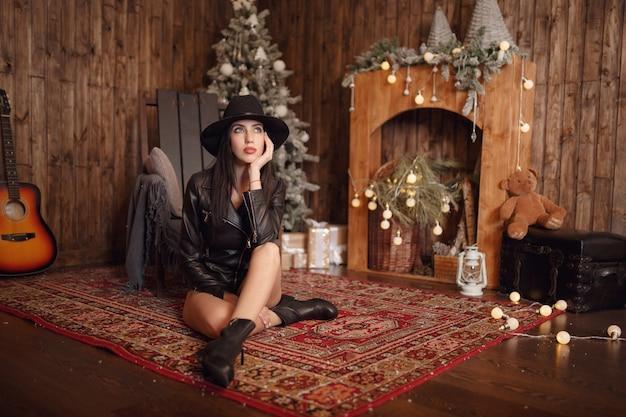 Bella giovane donna in lingerie nera sessuale e cappello nero in posa in decorazioni natalizie.