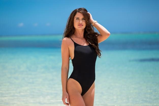 Bella giovane donna in bikini sexy in piedi sulla spiaggia del mare